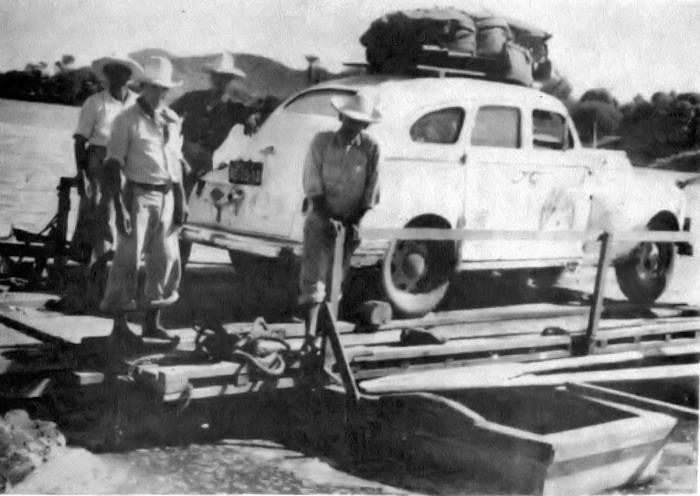 Expedition car on platform on two small boats.